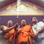 Lung Por Sam Ang Abbot of Wat Bang Pra sprays holy water on the devotees