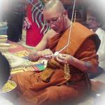 Luang Por Chanai is preparing white cords (Sinjana cords) for an amulet empowerment/Buddha Abhiseka.